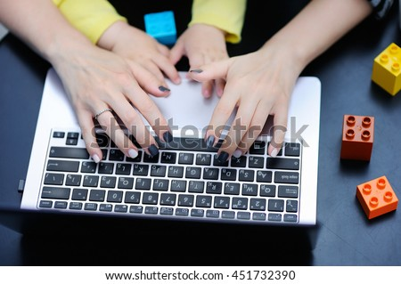 Close up photo of young mother working oh laptop with her toddler child - stock photo