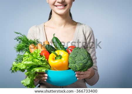 Close up photo of young woman standing against grey background. Woman smiling and holding big plate of fresh vegetables. Concept for healthy food - stock photo
