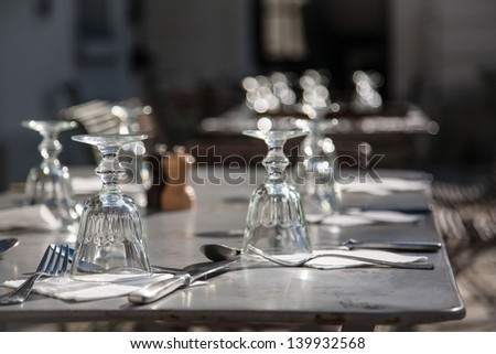 Close-up photo taken from the corner of a table with glasses, cuttlery and napkin on it and sun shines thruogh the glasses which makes them sparkling in the background