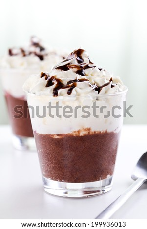 Close up photograph of a glass of chocolate mousse and whipped cream