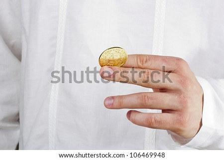 Close-up photograph of a golden coin between a man's fingers. - stock photo