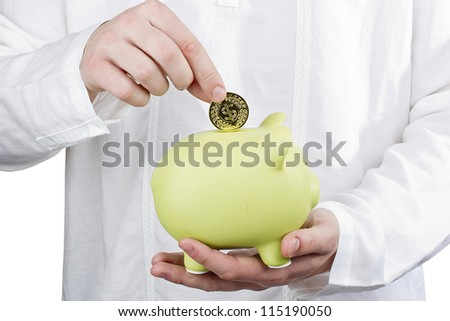 Close-up photograph of a man putting a coin in a green piggy bank. - stock photo