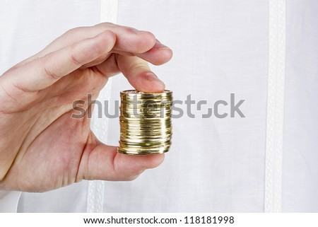 Close-up photograph of a man's hand holding a stack of coins. - stock photo