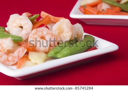 Close-up photograph of a shrimp salad on a white plate. - stock photo