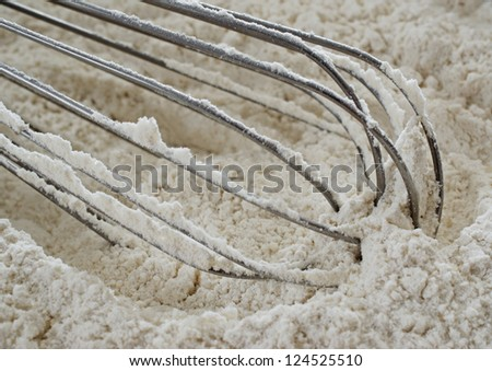 Close-up photograph of a stainless steel wire whisk in unbleached flour. - stock photo