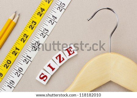 "Close-up photograph of a wooden hanger and measuring tape next to the word ""size"" on a gray background. - stock photo"