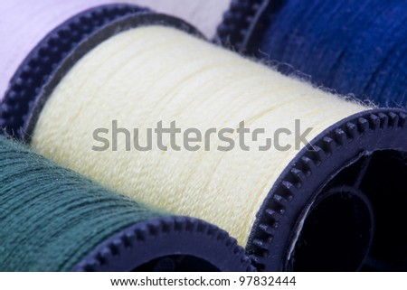 Close-up photograph of a yellow spool of thread among other spools. - stock photo