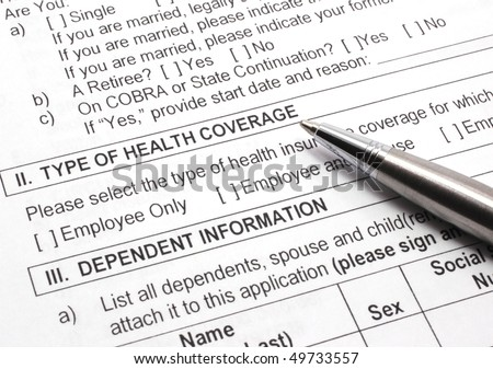 Close-up photograph of an employee group health insurance application form with pen.