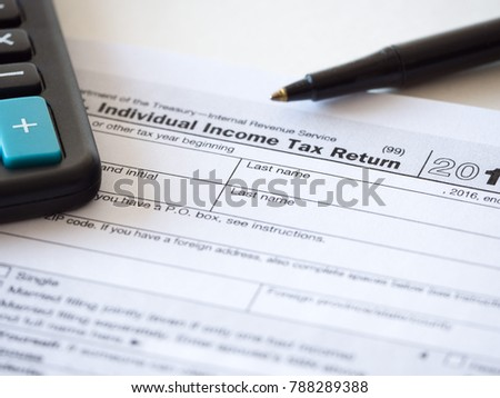 Close up photograph of individual income federal tax return paperwork with calculator and black ballpoint pen at borders for a nice tax season background, backdrop or wallpaper image.