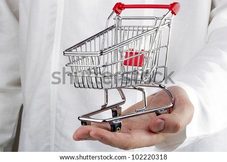 Close-up photograph of man's hand holding a shopping cart. - stock photo