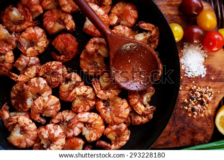 Close-up photos of colorful and appetizing,composition of the shrimp in a large black skillet, just fried over high heat in a sauce of soy sauce, garlic and olive oil, coarse salt from the sea, spices - stock photo