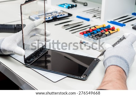 Close-up photos showing process of tablet device repair - stock photo