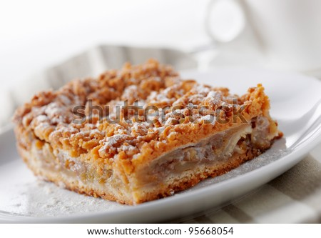 Close up picture of a baked pie on the plate with a cup at the back. - stock photo