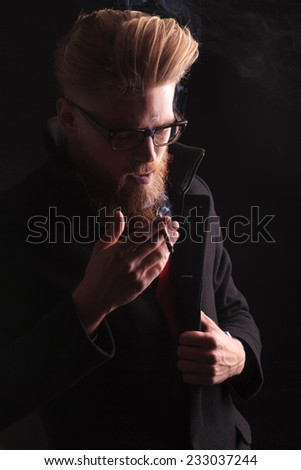 Close up picture of a beard fashion man looking down while enjoying his cigarette. - stock photo