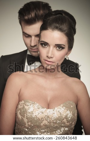 Close up picture of a beautiful woman posing together with her husband. He is standing behind her. - stock photo