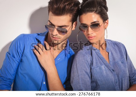 Close up picture of a casual fashion couple looking down, on studio background. - stock photo