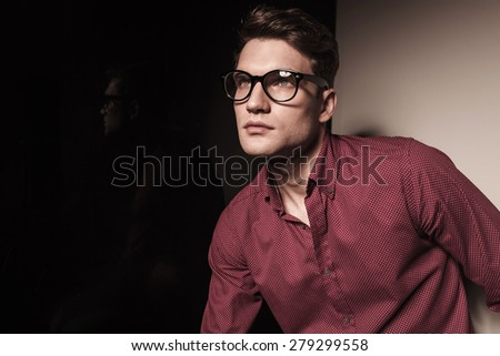 Close up picture of a casual young business man looking up.