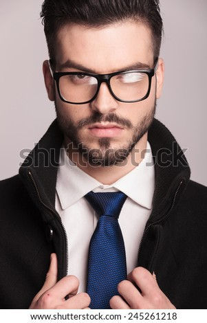 Close up picture of a elegant business man wearing glasses. He is fixing his coat while looking at the camera. - stock photo