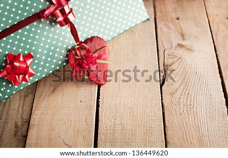 close up picture of a gift package and a heart on wooden background