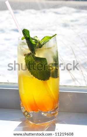 Close-up picture of a glass of Mojito cocktail with winter snow-covered street on the background