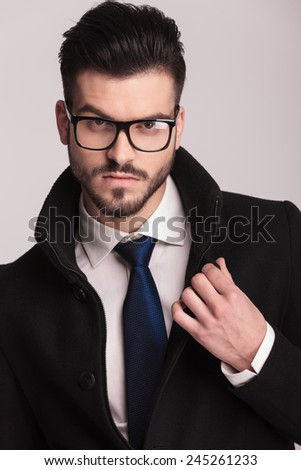 Close up picture of a handsome business man fixing his collar while looking at the camera.