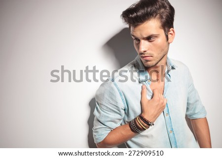 Close up picture of a handsome man pulling his shirt while looking down. - stock photo