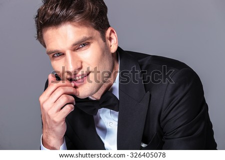 Close up picture of a handsome young business man holding his hand near the mouth. - stock photo