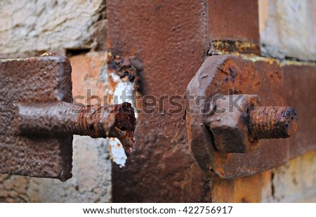 Close up picture of a rusty broken screw and a metal plate on it's side with one more screw and nut, all rusty and old. All elements on a rusty brown and white blurry background.