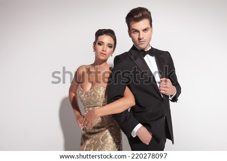 Close up picture of an elegant couple holding arms, both looking at the camera,