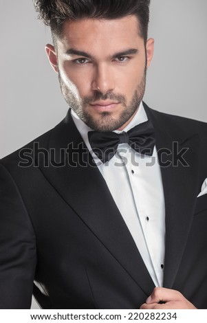Close up picture of an handsome young man in tuxedo ajusting his jacket, lokking at the camera. On grey background. - stock photo