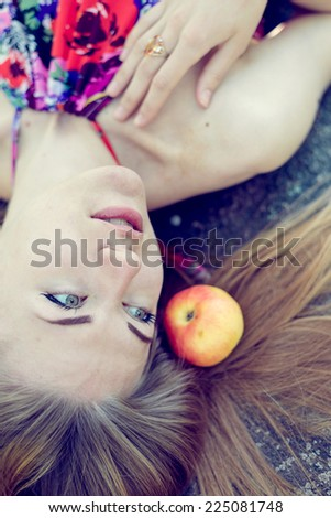 close up picture of beautiful blond young woman sensual pretty girl with blue eyes lying with apples on stone rock or ice ground & looking away on copy space portrait - stock photo