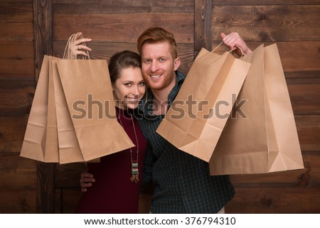 Close-up picture of cheerful couple demonstrating shopping bags over wooden background and smiling for the camera. - stock photo