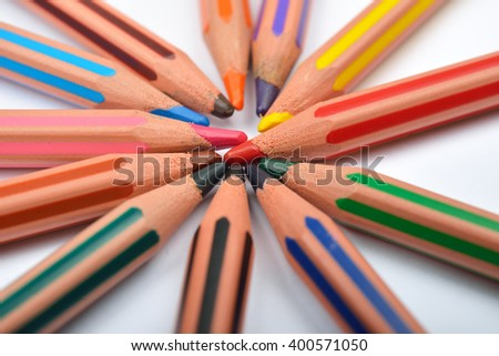 Close up picture of colored pencil crayons with stripes arranged in circle on white background. Assortment of colored pencils/ Colored drawing pencils. Selective focus - stock photo