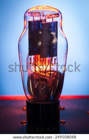 Close up picture of electronic vacuum tube,with incandescendent filament and white and blue background - stock photo
