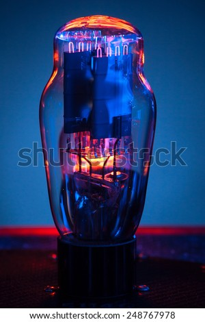 Close up picture of electronic vacuum tube,with incandescent filament and  blue background - stock photo