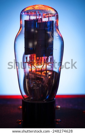 Close up picture of electronic vacuum tube,with incandescent filament and white and blue background - stock photo