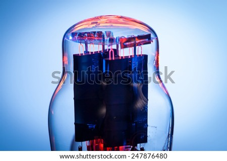 Close up picture of filaments of electronic vacuum tube rectifier. Blue and white background - stock photo