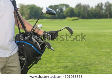 Close-up picture of golf bag hold by a golfer. Man in white T-shirt and cream trousers taking a driver to start his game over golf course.