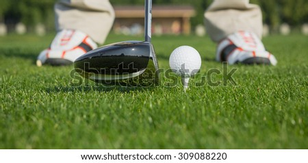 Close-up picture of golf ball behind driver at driving range, plenty of copy-space and very shallow depth of field. - stock photo