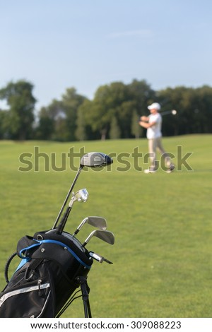 Close-up picture of golf clubs in golf bag isolated on green field background. Man playing professional golf on the background.