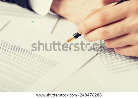 close up picture of man hand signing contract - stock photo