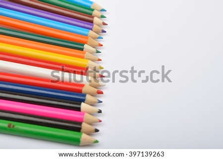 Close up picture of many little colored pencil crayons on white background. Assortment of sharpened colored pencils/ Colored drawing pencils. Selective focus. Copy space