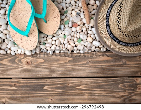 Close-up picture of many little sea shells on wooden. Flip-flops and straw hat for vacation are represented on beautiful shells. - stock photo