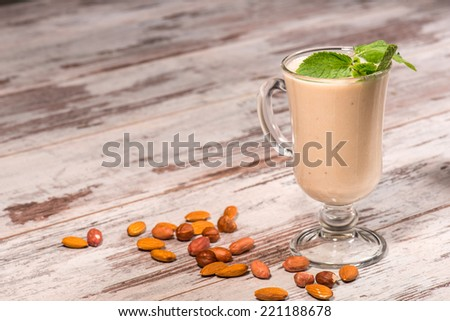 Close-up picture of tasty milk cocktail decorated with a leave of mint standing on the wooden table in cafe with different kind of nuts, with copy place - stock photo