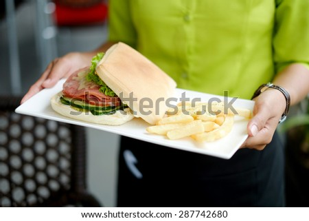 Close up picture of waiter holding food - stock photo