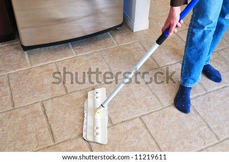 Close-up picture of woman's hand holding a mop cleaning kitchen floor - stock photo