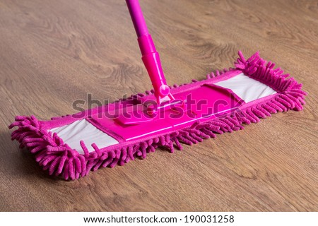 close up picture of wooden floor with pink cleaning mop - stock photo