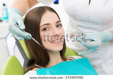 Close-up picture of young lady having her teeth examined by a dentist at dentist's office. Happy lady smiling for the camera.