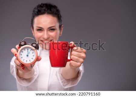 Close-up picture with selective focus alarm clock and a red cup in hands of young woman isolated on grey background with copy place concept of time management and coffee-break - stock photo