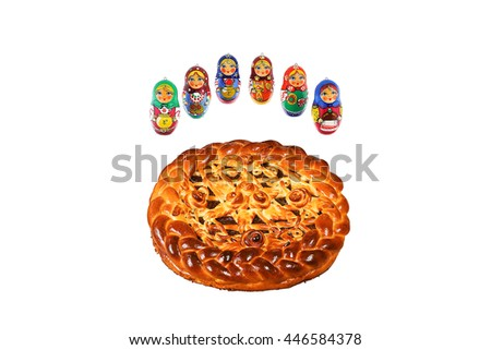 Close up pie surrounded by russian nesting dolls isolated. Culinary background, Russian kitchen.